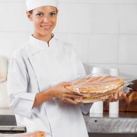 47937310 - portrait of smiling baker holding packed pizza breads in bakery