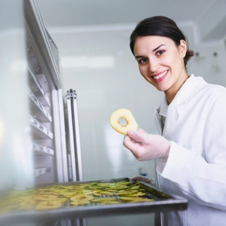 Smiling female engineer in front of food dryer dehydrator machine
