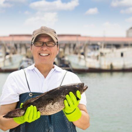 happy fisherman showing  fish before fishing ship